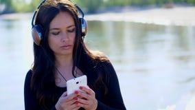 Verano, cerca del río, en la playa en la salida del sol, mujer hermosa, con el pelo oscuro largo, escuchando la música en los aur almacen de metraje de vídeo