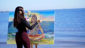 Verano, cerca del río, en la playa en la salida del sol, un artista hermoso de la mujer sostiene un cepillo, paleta en sus manos, metrajes