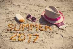 Verano 2017 de la inscripción, accesorios para tomar el sol y pasaporte con el dólar de las monedas en la arena Fotos de archivo libres de regalías