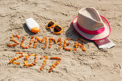 Verano 2017 de la inscripción, accesorios para tomar el sol y pasaporte con el dólar de las monedas en la playa Imagenes de archivo