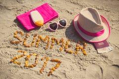 Verano 2017 de la inscripción, accesorios para tomar el sol y pasaporte con las monedas euro en la arena en la playa, tiempo de v Foto de archivo libre de regalías