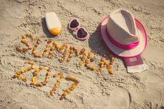 Verano 2017 de la inscripción, accesorios para tomar el sol y pasaporte con las monedas euro en la playa, concepto del tiempo de  Imagenes de archivo