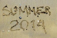 Verano 2014 de la inscripción en la playa del arena de mar Foto de archivo libre de regalías