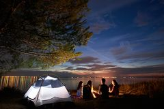 Verano de la noche que acampa en orilla Grupo de turistas jovenes alrededor de la hoguera cerca de la tienda debajo del cielo de  imagen de archivo libre de regalías