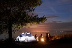 Verano de la noche que acampa en orilla Grupo de turistas jovenes alrededor de la hoguera cerca de la tienda debajo del cielo de  imagenes de archivo