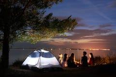 Verano de la noche que acampa en orilla Grupo de turistas jovenes alrededor de la hoguera cerca de la tienda debajo del cielo de  fotos de archivo libres de regalías