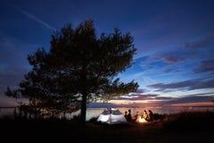 Verano de la noche que acampa en orilla Grupo de turistas jovenes alrededor de la hoguera cerca de la tienda debajo del cielo de  fotografía de archivo