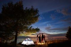 Verano de la noche que acampa en orilla Grupo de turistas jovenes alrededor de la hoguera cerca de la tienda debajo del cielo de  fotos de archivo