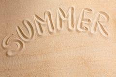 Verano de la palabra escrito cerca en la arena Imágenes de archivo libres de regalías
