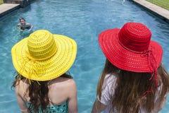 Verano de la piscina del muchacho de los sombreros de las muchachas Foto de archivo libre de regalías