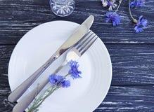 Verano del arreglo del diseño del abastecimiento del menú de los acianos de las flores, placa, cuchillo de la bifurcación en un f Imagenes de archivo