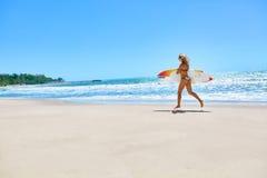 verano El practicar surf Deporte del verano Mujer con el funcionamiento de la tabla hawaiana Foto de archivo libre de regalías