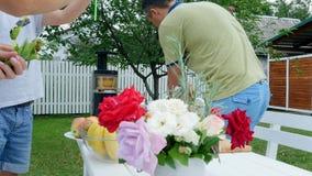 Verano, en el jardín, la familia fija la tabla, madre y el hijo hace un ramo de las flores, alimentaciones del padre su hija con metrajes