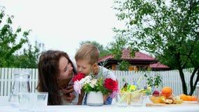 Verano, en el jardín La mamá con un hijo de cuatro años hace un ramo de flores El muchacho le gusta él mucho, divirtiéndose almacen de video