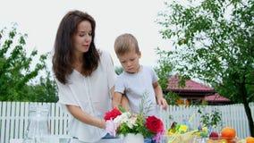 Verano, en el jardín La mamá con un hijo de cuatro años hace un ramo de flores El muchacho le gusta él mucho, él es feliz metrajes