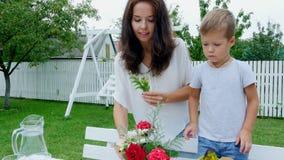 Verano, en el jardín La mamá con un hijo de cuatro años hace un ramo de flores El muchacho le gusta él mucho, él es feliz almacen de video