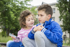 Verano en el parque un pequeño muchacho rizado-cabelludo muestra su mún brazo a Fotos de archivo libres de regalías