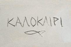 Verano en griego escrita en la arena Imagenes de archivo