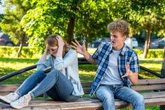 Verano en naturaleza El individuo grita en la muchacha que gesticula con sus manos La muchacha cubrió su cabeza con las manos que Imagenes de archivo