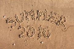 Verano 2016 escrito en la arena en los rayos del sol Imagen de archivo
