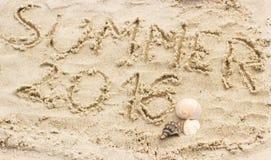 Verano 2016 exhausto en la arena y cáscaras en la playa Foto de archivo libre de regalías