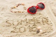 Verano 2016 exhausto en la arena y el corazón de cáscaras con las gafas de sol Foto de archivo libre de regalías