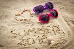 Verano 2016 exhausto en la arena y el corazón de cáscaras con las gafas de sol Imágenes de archivo libres de regalías