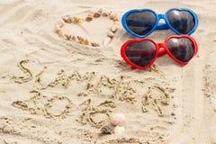 Verano 2016 exhausto en la arena y el corazón de cáscaras con las gafas de sol Imagen de archivo