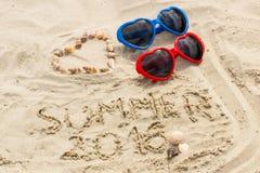 Verano 2016 exhausto en la arena y el corazón de cáscaras con las gafas de sol Fotos de archivo