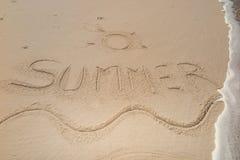 verano manuscrito en la arena, el fondo del verano, el mar y el fondo de la arena Foto de archivo libre de regalías