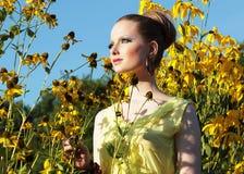Verano. Muchacha en prado entre las flores amarillas Fotos de archivo