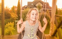 Verano - niño feliz de la muchacha del niño en el jardín en el oscilación Imagen de archivo