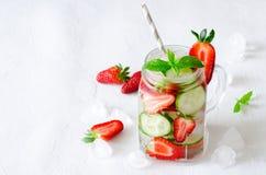 Verano que restaura bebidas heladas con el pepino y la fresa en el fondo blanco Imágenes de archivo libres de regalías