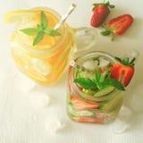Verano que restaura bebidas heladas con la naranja, el limón, el pepino y la fresa en el fondo blanco Imagenes de archivo