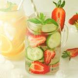Verano que restaura bebidas heladas con la naranja, el limón, el pepino y la fresa en el fondo blanco Foto de archivo libre de regalías