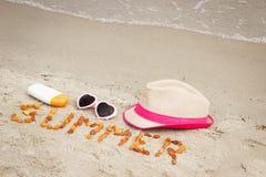 Verano y accesorios de la inscripción para las vacaciones en la arena en la playa, protección del sol, tiempo de verano Imagenes de archivo