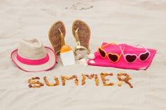 Verano y accesorios de la inscripción para las vacaciones en la arena en la playa, protección del sol, tiempo de verano Foto de archivo libre de regalías