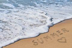 Verano y corazón de la palabra en la arena de la playa fotos de archivo