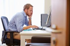 Överansträngd manlig doktor In Office Sitting på datoren Royaltyfri Bild