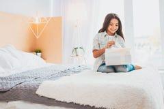 Verantwoordelijk meisje die verjaardagsgeschenk ontvangen die in lichte slaapkamer zijn stock foto's