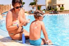 Verantwoordelijke moeder die zonnescherm op haar zoon toepassen stock foto