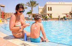Verantwoordelijke moeder die zonnescherm op haar zoon toepassen royalty-vrije stock foto's