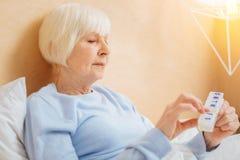 Verantwortlicher aufmerksamer Pensionär, der eine Pille von ihrer Pillenschachtel und von Denken einnimmt stockfotografie