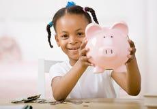 Verantwortliches Mädchen, das Geld in piggy Querneigung steckt Lizenzfreies Stockfoto