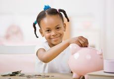 Verantwortliches Mädchen, das Geld in piggy Querneigung steckt Lizenzfreie Stockfotos