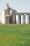 Verarbeitungsanlage des Kornes mit Feld im Vordergrund Lizenzfreie Stockfotos