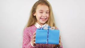 Verbaasd jong meisje die een gift ontvangen Het schot van de studio stock videobeelden