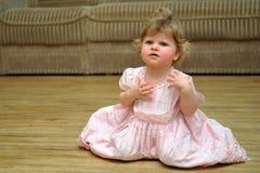 Verbaasd klein meisje in roze kleding op houten vloer Royalty-vrije Stock Foto's