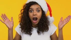 Verbaasd meisje die in die Kerstmanhoed, aangenaam wauw zeggen door Nieuwjaargiften wordt verrast stock video