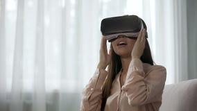 Verbaasd meisje die die VR-hoofdtelefoon voor eerste keer met behulp van, met positieve emoties wordt overweldigd stock video